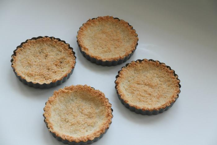 Minipaier med bunn laget av kokos, sukker og eggehvite. Fylt med sitronkrem og toppet med ferske bær. Disse paiene er supergode og enkle å lage.